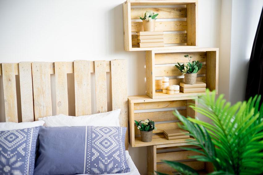 des caisses en bois superposées forme une table de chevet dans la chambre à coucher