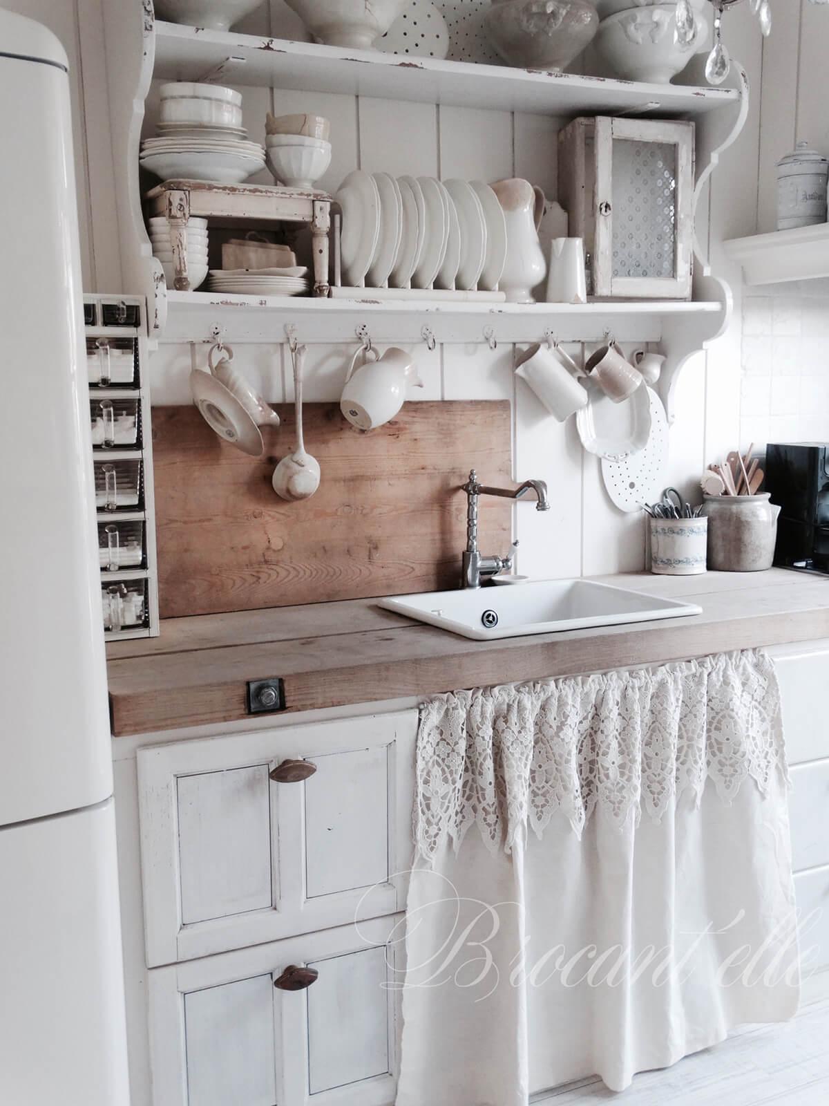 Cuisine style country avec étagères en bois et petit rideau sous lavabo.